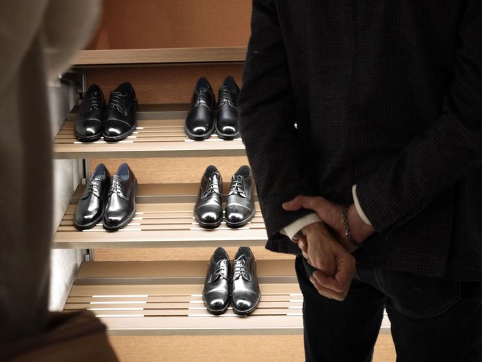 Midsection of man standing with hands behind back against shoes on rack at store