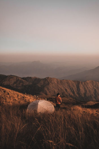 Man on field by mountain against sky during sunset