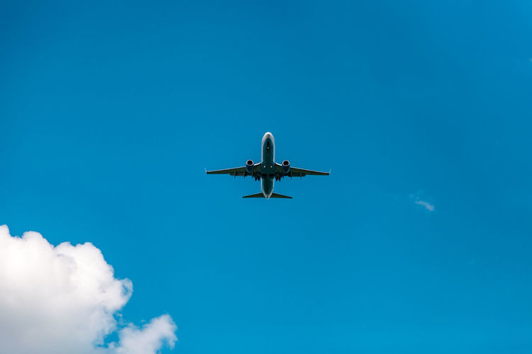 Low angle view of airplane against blue sky