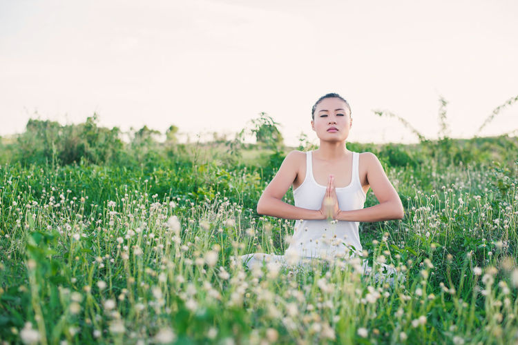 Young woman practicing yoga on grassy field