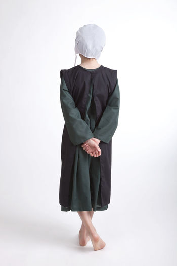 Young Amish girl in green dress with black apron and white bonnet Amish Apron Black Bonnet Cape  Cotton Cute Dress Facing Away Girl Green One Person Religion Sad White Young