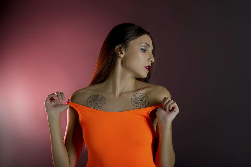 Sensuous woman undressing against colored background