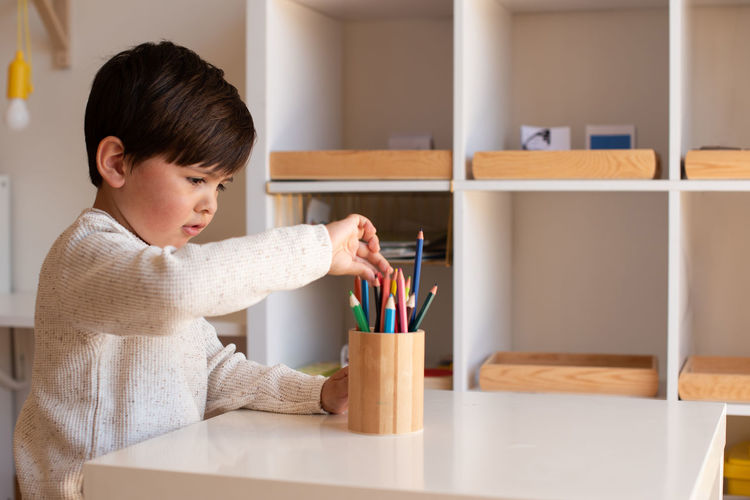 Boy holding table at home