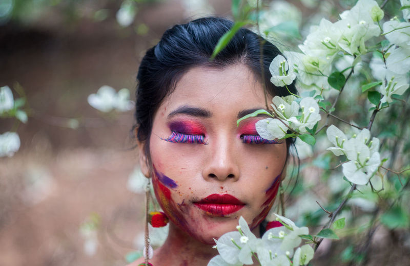 Young woman with eyes closes standing by flowering plant