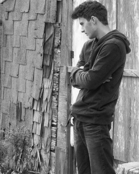 Thoughtful Young Man With Arms Crossed Standing By Old House
