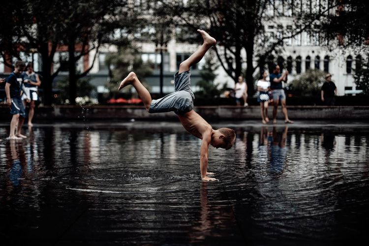 Boy doing handstand in water puddle