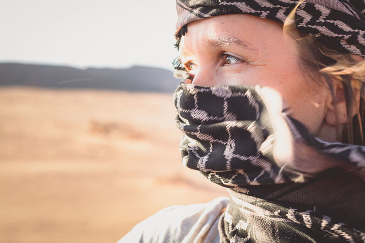 Close-Up Of Woman Covering Face With Scarf In Desert Against Sky