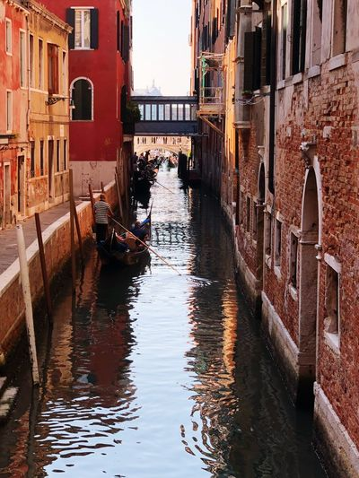 Man standing in gondola on canal against buildings
