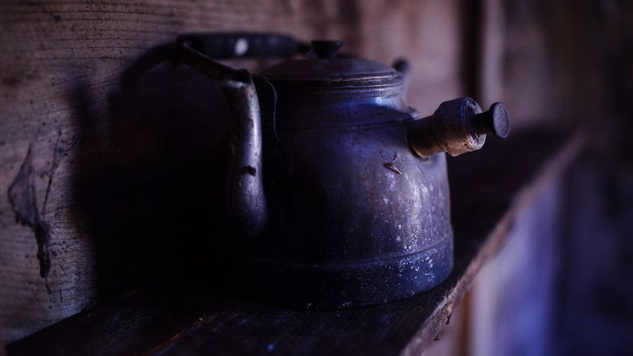 Close-up of old-fashioned tea kettle in darkroom