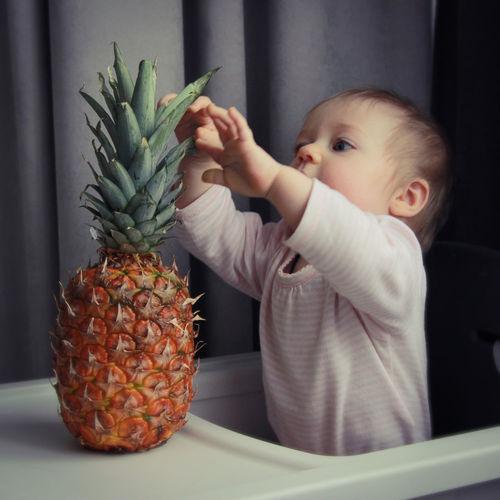 Baby girl holding pineapple fruit