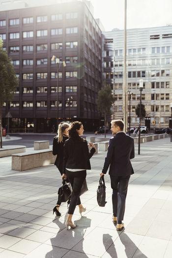 People walking on footpath against buildings in city