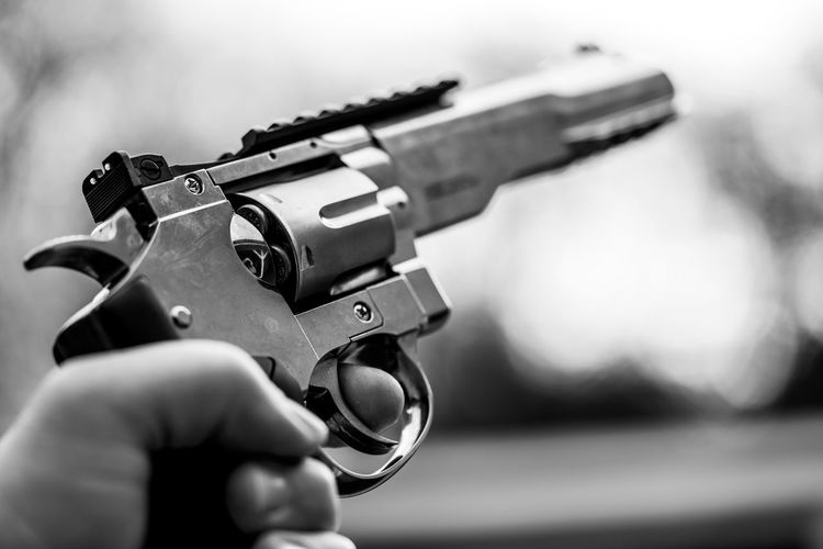 Close-up of cropped hand holding gun