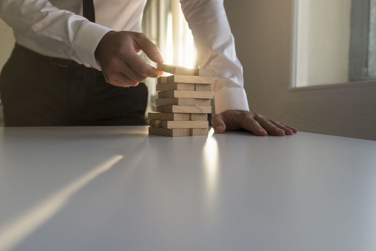 Rear view of a man holding stack of table