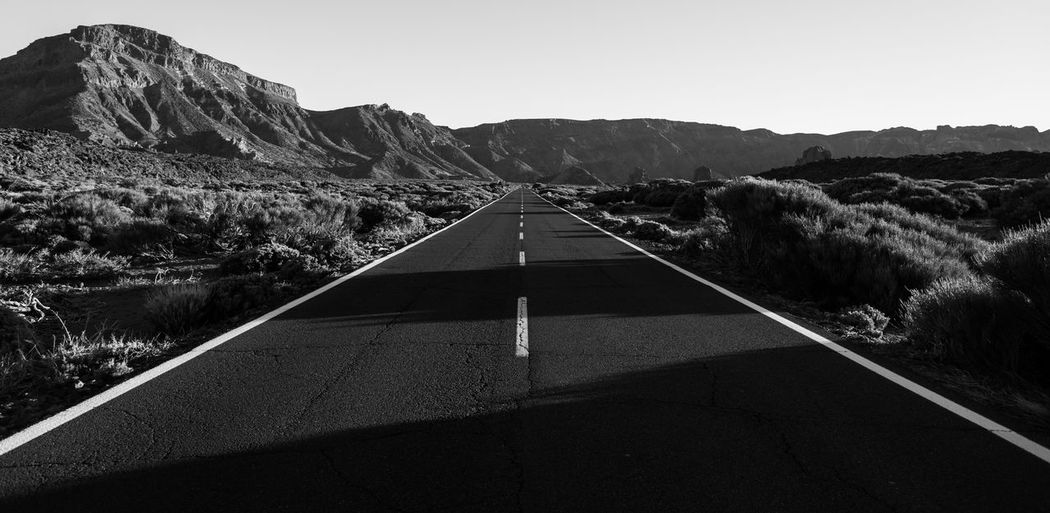 Road by mountains against clear sky