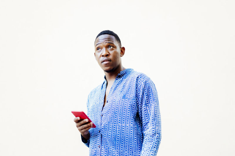 Young man looking away while standing against white background
