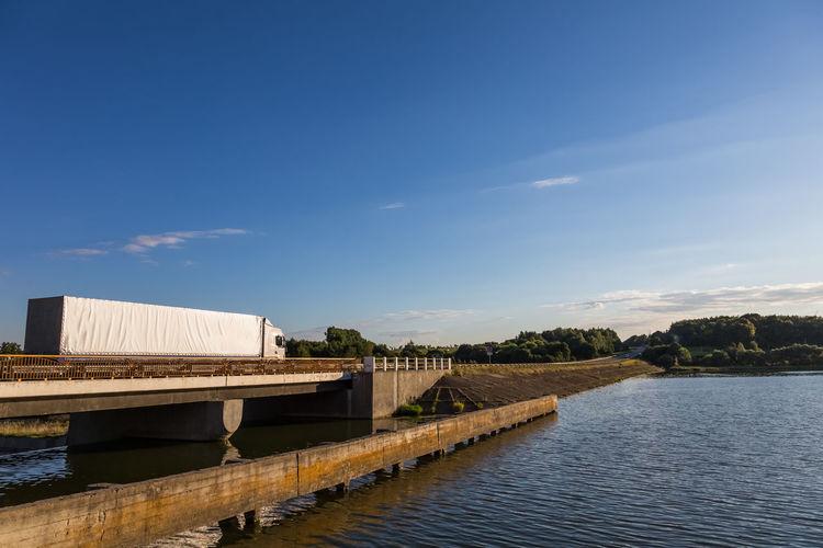 Truck on bridge over river against sky