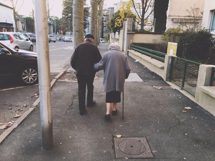 Rear view of senior couple walking on street