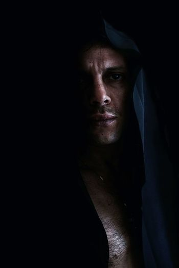 Portrait Of Man In Hood Clothing Against Black Background