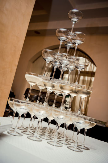 Champagne glass pyramid Aperitif Banquet Celebration Champagne Pyramid Champagne Glass Pyramid Champagne Glasses Cocktail Pyramid Wedding Wedding Reception Banquet Table Champagne Flute Champagne Fountain Champagne Tower Glass Pyramid In A Row Indoors  Lot No People Party Pyramid Shape Restaurant Table Tablecloth Wedding Banquet