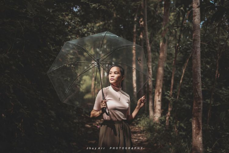 Full length of woman standing by tree during rainy season