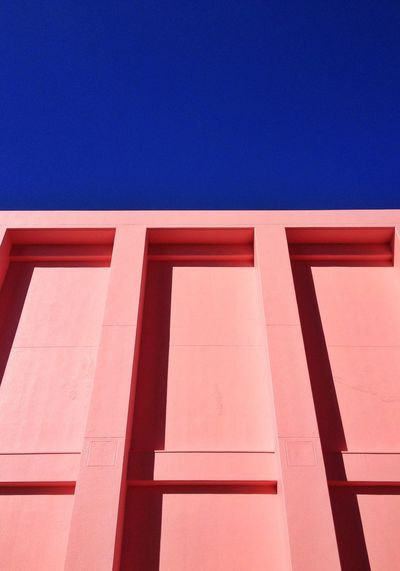 Low angle view of pink wall against clear blue sky