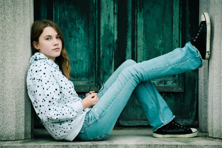 Portrait of a young woman sitting on door