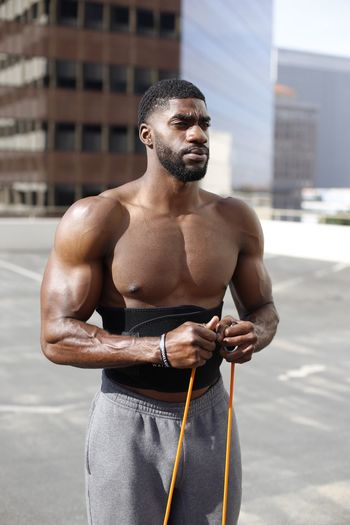 Shirtless Muscular Man Standing Against Buildings