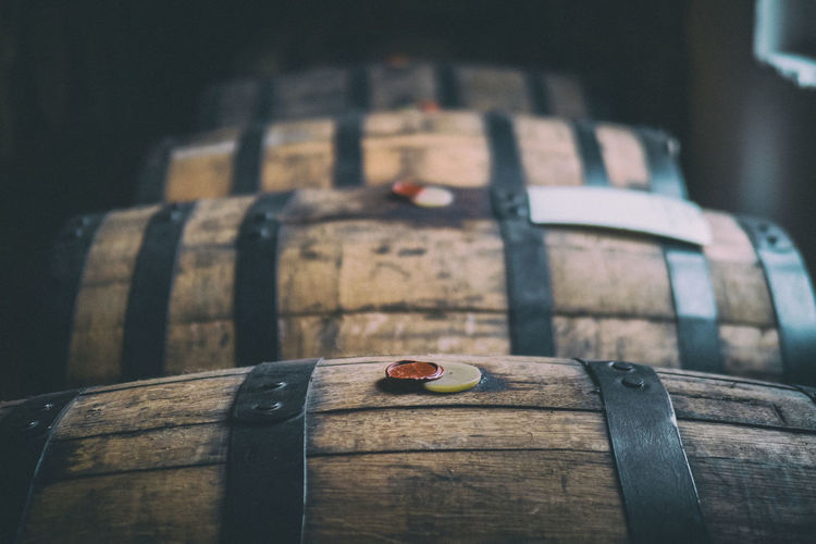 Whisky in wooden barrels with tax seals aging near a window