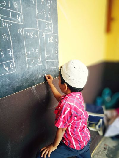 Side view of boy writing on blackboard while standing in classroom