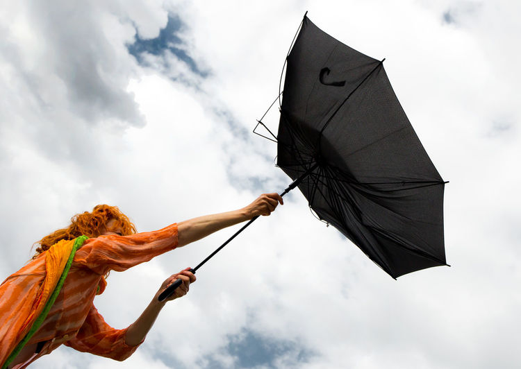Low angle view of mature woman holding damaged umbrella against cloudy sky