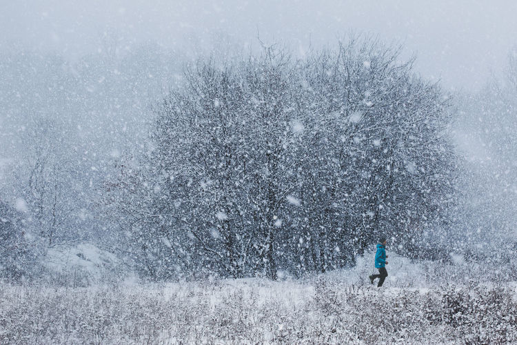 Side view of teenage boy running on field during snowfall in forest
