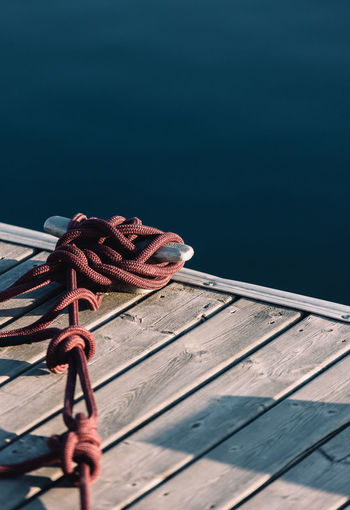 Rope tied in knots on pier at marina.