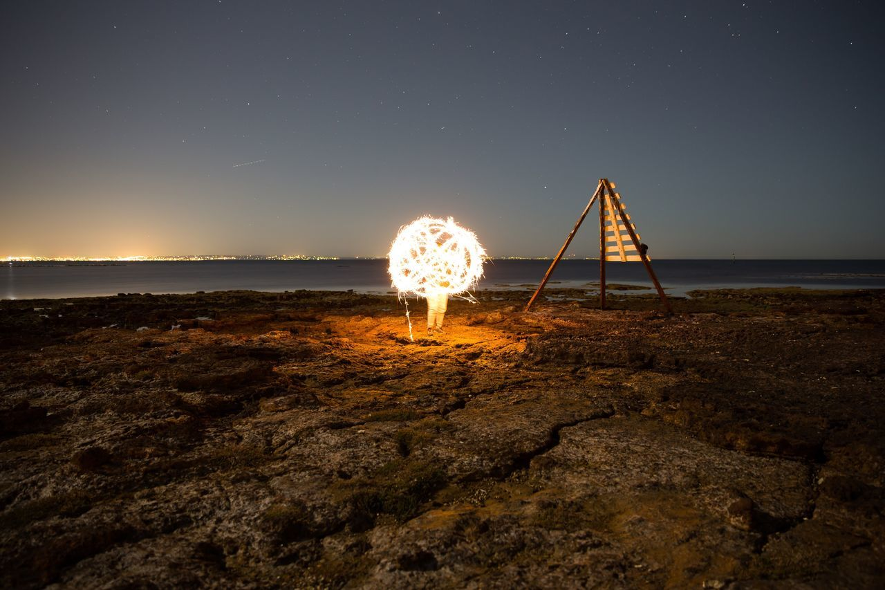 Man by burning wire wool at rocky shore