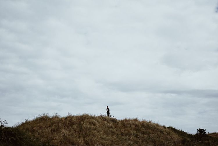 Man With Bicycle Standing On Grassy Hill Against Cloudy Sky