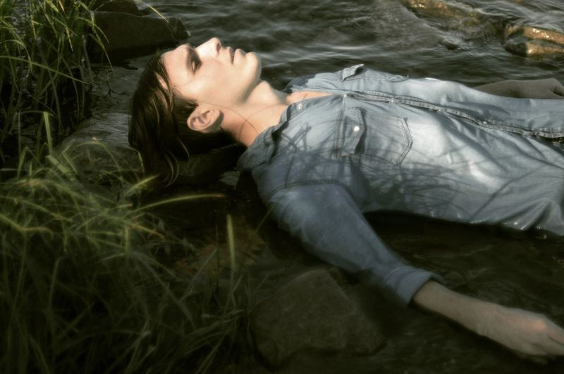 Man Lying In River At Forest