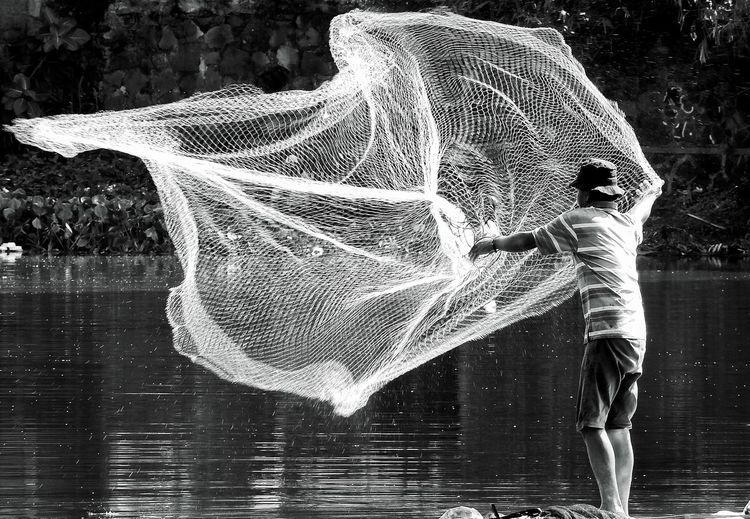 Spread your net and catch the fish Water Real People One Person Splashing Lifestyles Nature Leisure Activity Waterfront Three Quarter Length Standing Outdoors Day Wet Motion Sunlight Men Childhood Child