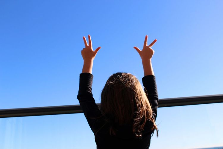 Rear view of girl gesturing against clear blue sky