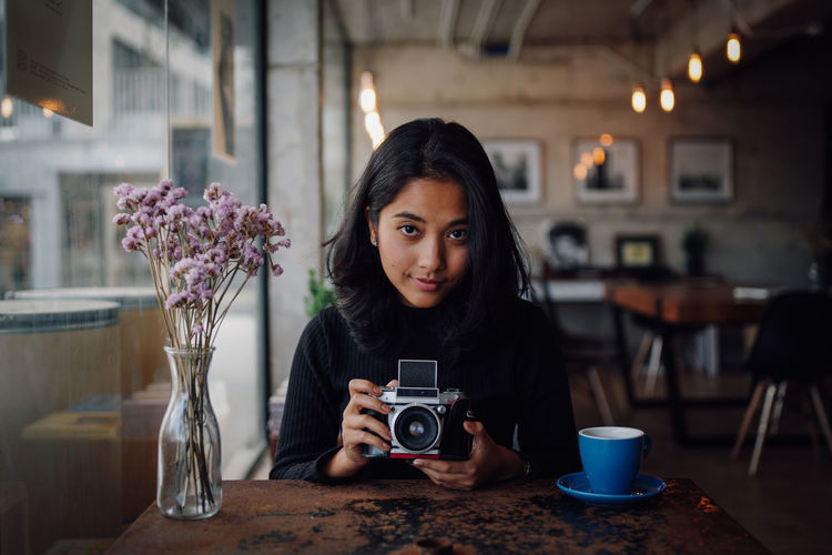 Beautiful Woman Camera - Photographic Equipment Focus On Foreground Front View Hair Hairstyle Headshot Holding Indoors  Leisure Activity Lifestyles Looking At Camera One Person Photographer Photographing Photography Themes Portrait Real People Sitting Table Technology Young Adult Young Women