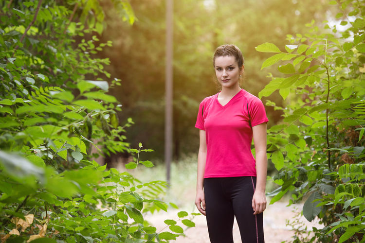 Woman standing by pink tree