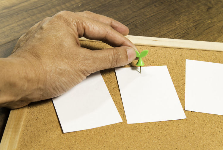 Cropped Hand Of Man Holding Thumbtack With Paper On Bulletin Board