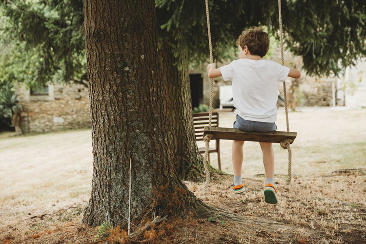 Rear view of boy standing on tree trunk
