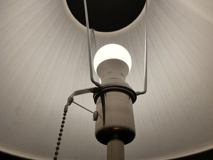 Low angle view of illuminated electric lamp on ceiling