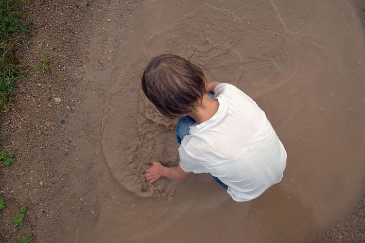 Directly above shot of girl playing in muddy water