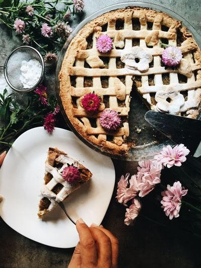 High angle view of pie in plate by flowers on table