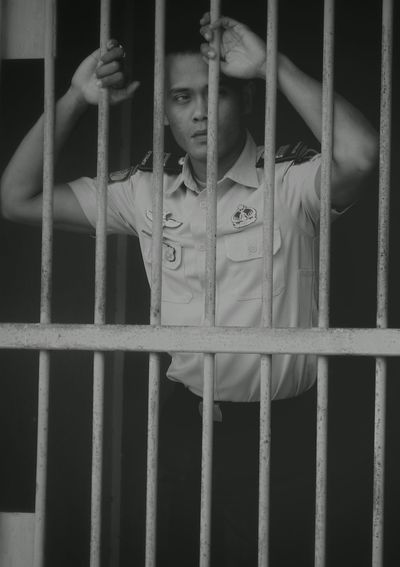 Guard standing behind prison cell