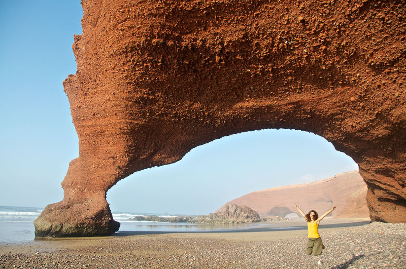 Woman Jumping On Beach Against Rock Formation