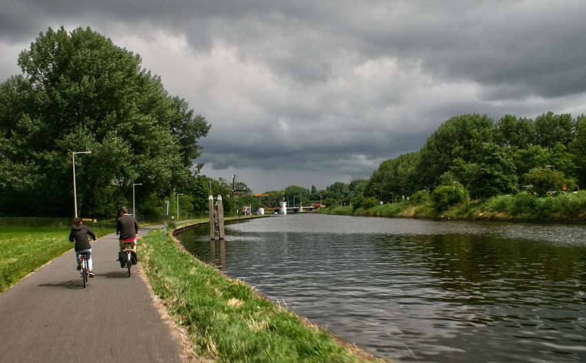 Rear View Of Friends Riding Bicycles On Road By River Against Cloudy Sky