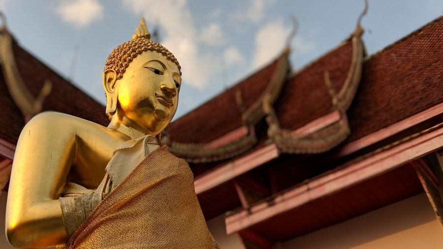 Low angle view of buddha statue against temple