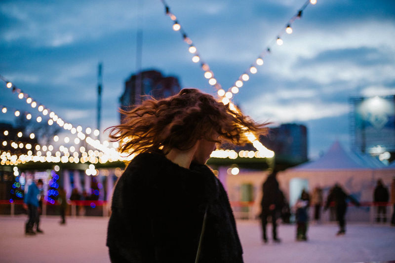 Woman shaking head against illuminated lights at dusk