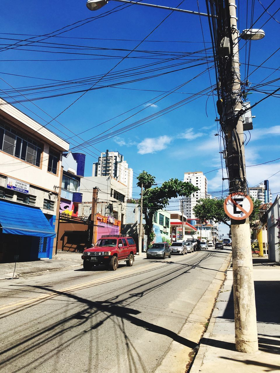 building exterior, city, architecture, transportation, cable, built structure, sky, mode of transportation, street, nature, power line, electricity, car, sunlight, day, motor vehicle, road, building, land vehicle, shadow, outdoors, no people, power supply, track, telephone line, complexity